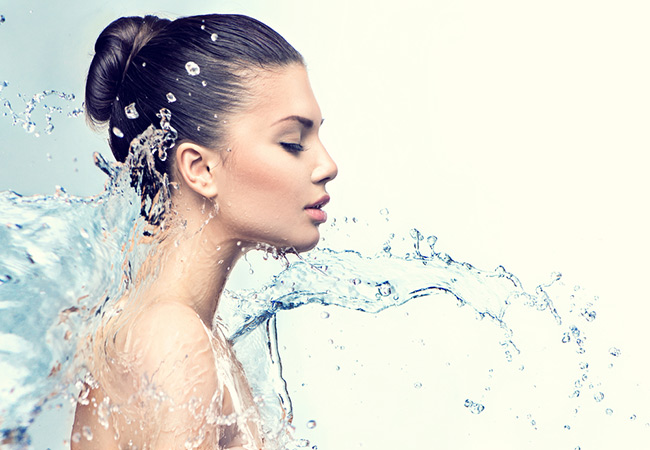 model spashing water on face