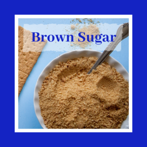 brown sugar in white bowl with a spoon on blue background