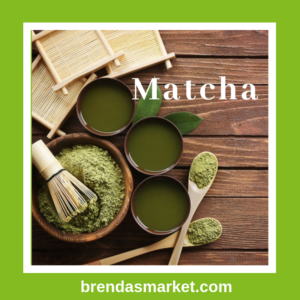 matcha powder in wooden bowl and wooden spoons beside three bowls of matcha tea